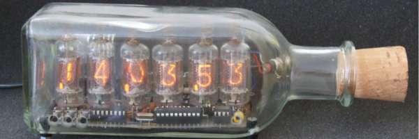 Une horloge avec des lampes à tubes dans une bouteille.