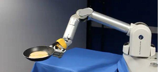 Le robot qui fait sauter les crêpes dans une poêle après apprentissage.
